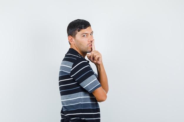 Junger mann im t-shirt, das stillegeste zeigt und vorsichtig schaut.