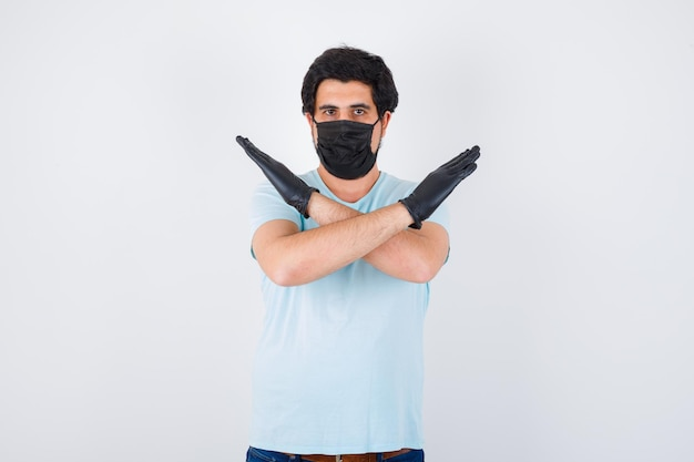 Junger mann im t-shirt, das stoppgeste zeigt und ängstlich aussieht, vorderansicht.