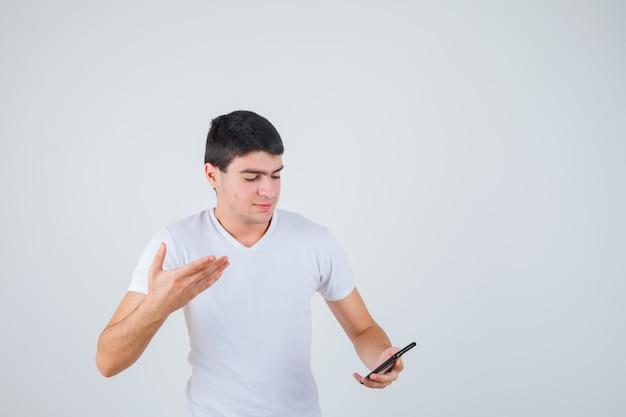 Junger mann im t-shirt, das telefon hält, während hand hebt und fokussierte vorderansicht schaut.