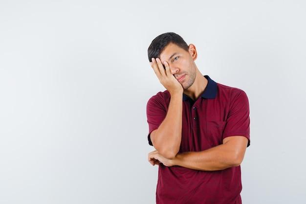 Junger mann im t-shirt, der den kopf auf die erhobene handfläche lehnt und müde aussieht, vorderansicht.