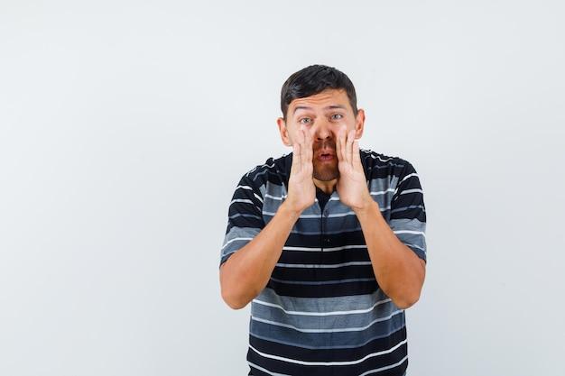 Junger mann im t-shirt, der geheimnis erzählt, indem er die hände in der nähe des mundes hält, vorderansicht.