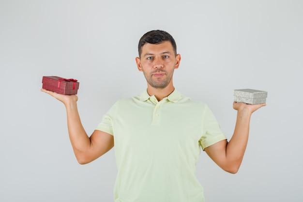 Junger mann im t-shirt, der geschenkboxen hält und froh aussieht