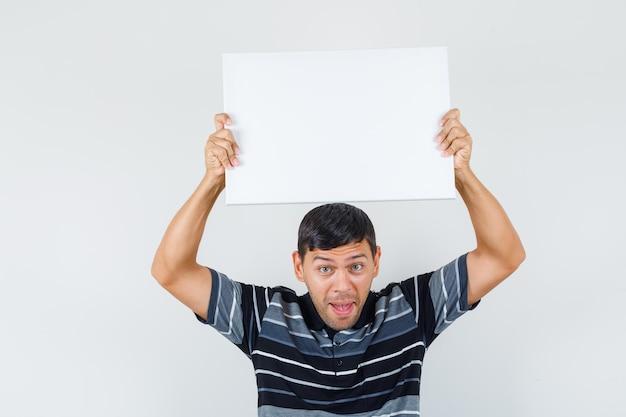Junger mann im t-shirt, der leere leinwand über dem kopf hält und glückselig aussieht, vorderansicht.
