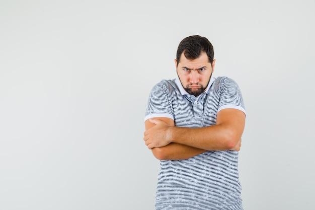 Junger mann im t-shirt, der mit eng verschränkten armen steht und beleidigt aussieht, vorderansicht.
