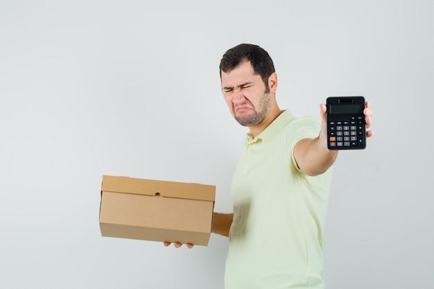 Junger mann im t-shirt, der pappkarton und taschenrechner hält und traurig, vorderansicht schaut.
