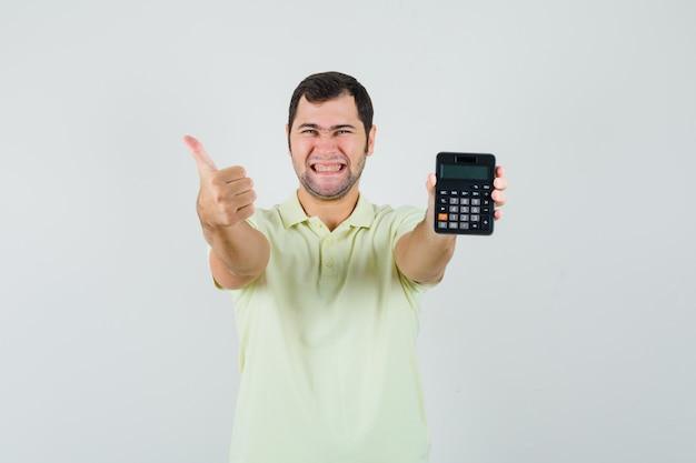 Junger mann im t-shirt, der rechner hält, zeigt daumen hoch und schaut fröhlich, vorderansicht.