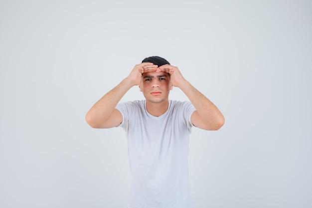 Junger mann im t-shirt, der weit weg mit hand über kopf schaut und fokussierte vorderansicht schaut.