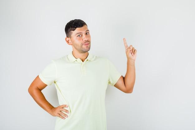 Junger mann im t-shirt, der zeigefinger mit hand auf taille anhebt und zuversichtlich schaut