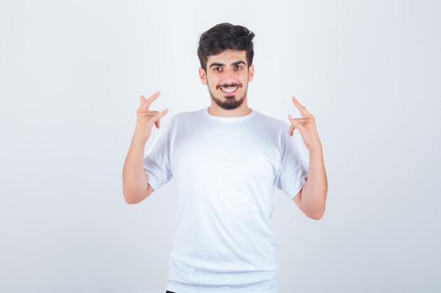 Junger mann im t-shirt, der zeigt, dass ich dich liebe, geste und fröhlich aussehend