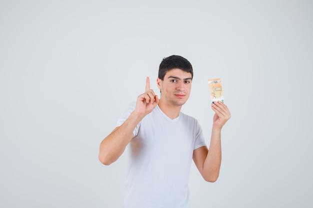 Junger mann im t-shirt hält eurobanknote, zeigt nach oben und schaut selbstbewusst, vorderansicht.