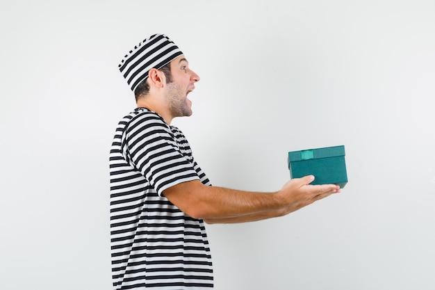 Junger mann im t-shirt, hut, der geschenkbox präsentiert und glücklich schaut.