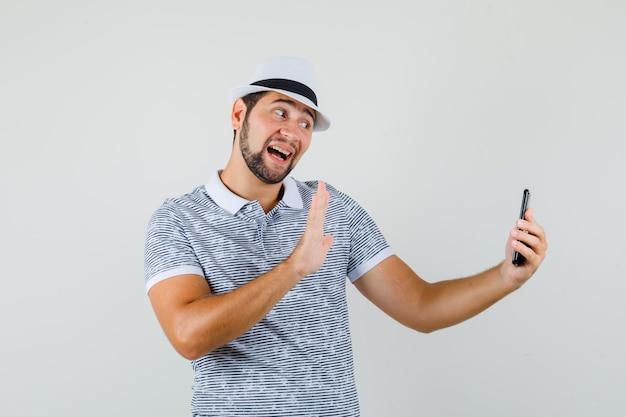 Junger mann im t-shirt, hut, der hand wendet, während videoanruf tut und fröhlich schaut, vorderansicht.