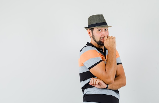Junger mann im t-shirt, hut, der in denkender haltung steht und unruhig schaut, vorderansicht.