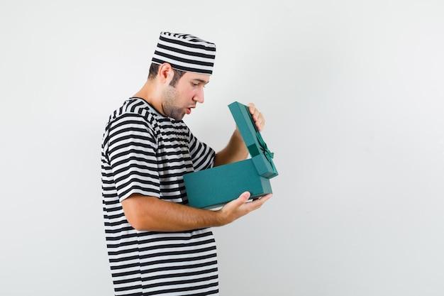 Junger mann im t-shirt, hut, der in geschenkbox schaut und überrascht schaut.
