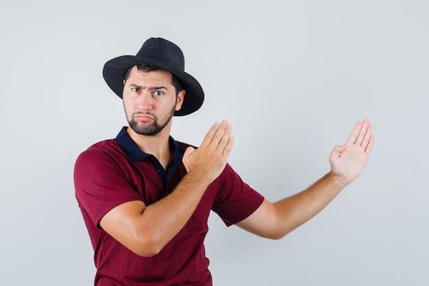 Junger mann im t-shirt, hut, der karate-hiebgeste zeigt und wütend, vorderansicht schaut.