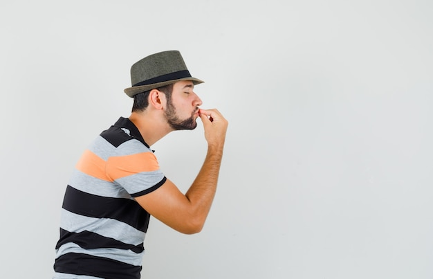 Junger mann im t-shirt, hut, der köstliche geste zeigt, indem er finger küsst und entzückt aussieht.