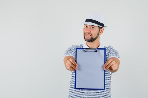 Junger mann im t-shirt, hut, der sein notizbuch zeigt, vorderansicht.