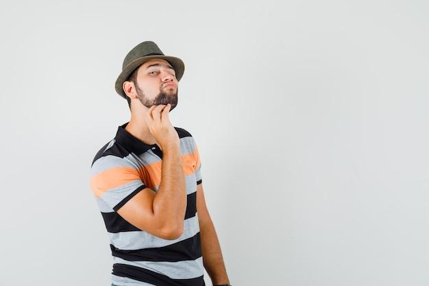 Junger mann im t-shirt, hut, der seine gesichtshaut durch berühren des bartes überprüft und elegant, vorderansicht schaut.