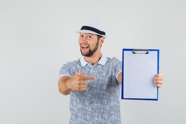 Junger mann im t-shirt, hut zeigt auf sein notizbuch und schaut bereit, vorderansicht.