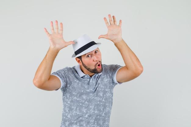 Junger mann im t-shirt, hut zeigt zehn finger und sieht glücklich aus, vorderansicht.