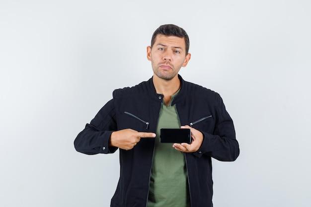 Junger mann im t-shirt, jacke, die auf handy zeigt und verzweifelt aussieht, vorderansicht.