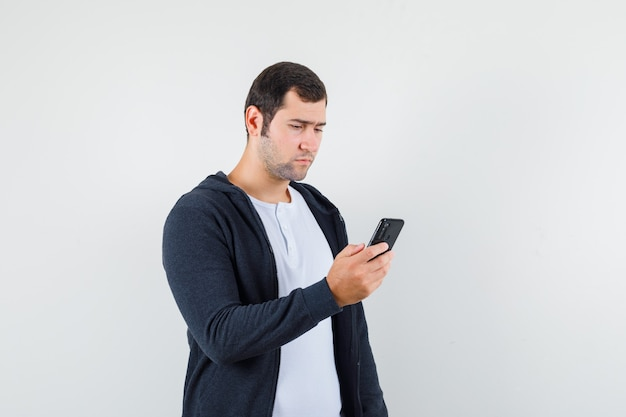 Junger mann im t-shirt, jacke, die handy benutzt und beschäftigt schaut, vorderansicht.