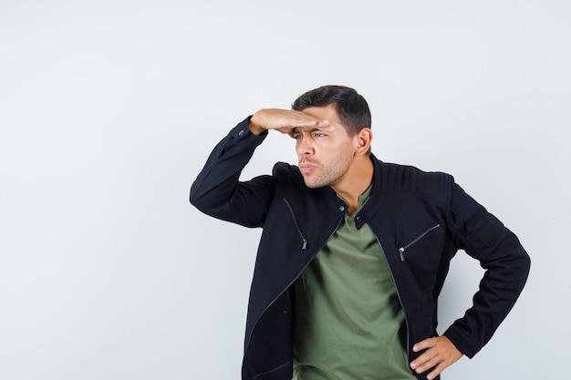 Junger mann im t-shirt, jacke, die mit der hand über dem kopf weit weg schaut und fokussiert aussieht, vorderansicht.