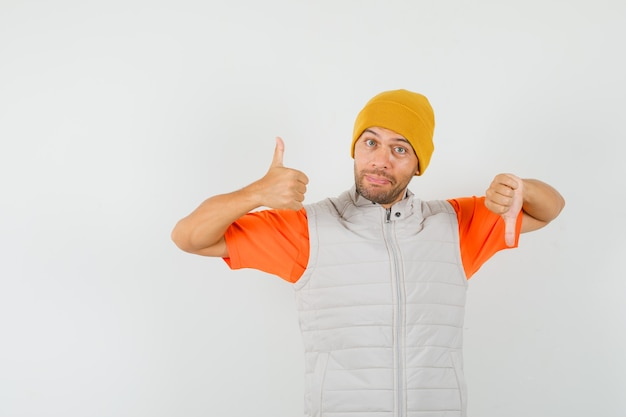 Junger mann im t-shirt, jacke, hut, der daumen oben und unten zeigt, vorderansicht.