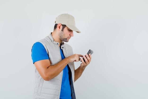 Junger mann im t-shirt, jacke mit taschenrechner und blick beschäftigt, vorderansicht.
