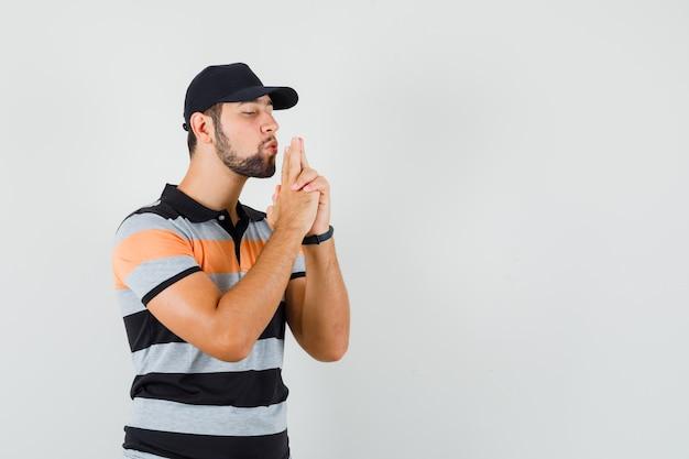 Junger mann im t-shirt, mütze, die auf pistole bläst, die von händen gemacht wird und selbstbewusst aussieht, vorderansicht.