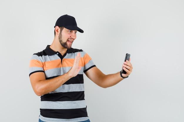 Junger mann im t-shirt, mütze, die hand auf video-chat winkt und fröhlich schaut, vorderansicht.