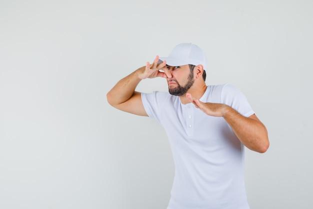 Junger mann im t-shirt, mütze, die seine nase fängt und ekelhaft aussieht, vorderansicht.