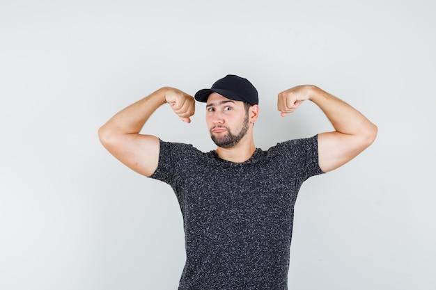Junger mann im t-shirt und in der kappe, die muskeln zeigen und stark schauen