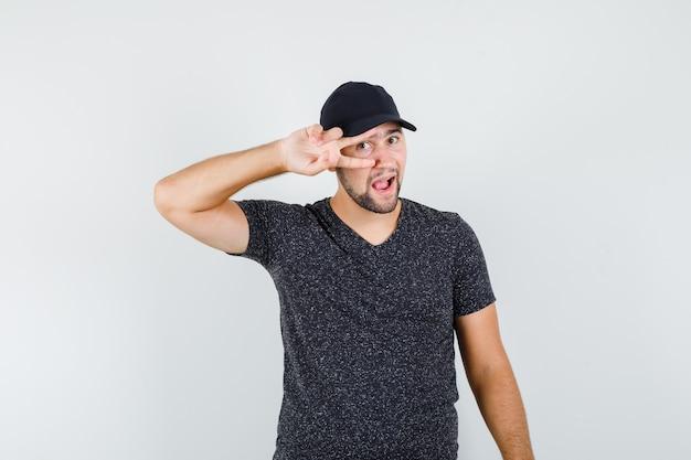 Junger mann im t-shirt und in der kappe, die v-zeichen auf auge halten