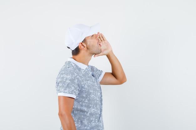 Junger mann im t-shirt und in der mütze, die schreien, um um hilfe zu bitten.