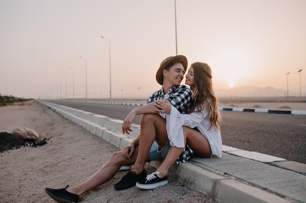 Junger mann im trendigen hut, der mit liebe auf seine anmutige freundin im weißen hemd schaut, während er nach dem gehen ruht. paar reisende sitzen in der nähe der straße und umarmen sich sanft mit sonnenuntergang