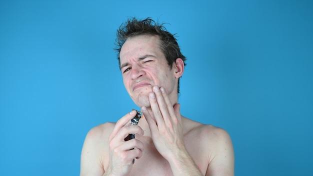 Junger mann im unbehagen beim rasieren.