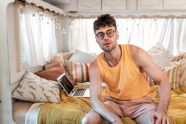 Junger mann im urlaub mit dem wohnmobil. unterwegs mit dem wohnwagen. konzept über fernweh-roadtrips und lifestyle im urlaub