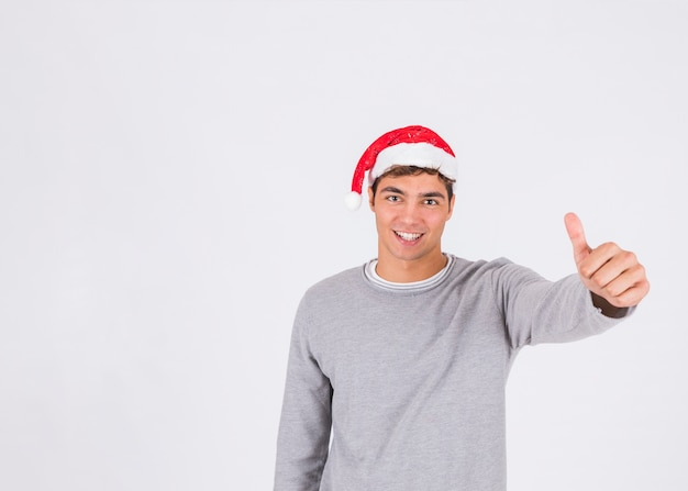 Junger mann im weihnachtshut mit dem daumen oben
