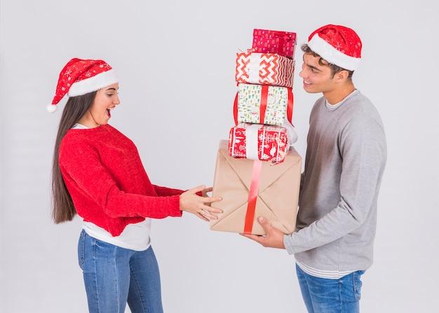 Junger mann im weihnachtshut mit haufen von geschenken nähert sich überraschter frau