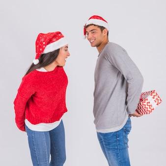 Junger mann im weihnachtshut mit präsentkarton nahe attraktiver frau