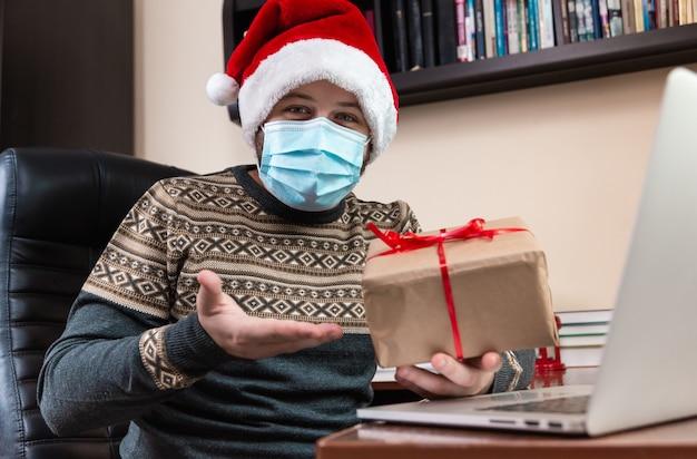 Junger mann im weihnachtsmannhut und in der gesichtsmaske gibt ein geschenk und spricht unter verwendung des laptops für videoanruffreunde und -kinder. weihnachten während des coronavirus.