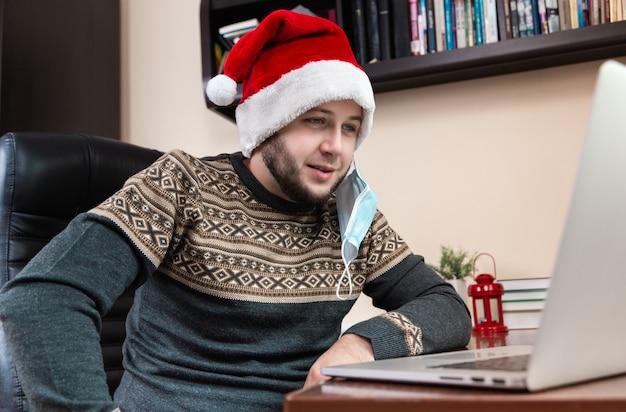 Junger mann im weihnachtsmannhut und in der gesichtsmaske spricht unter verwendung des laptops für videoanruffreunde und -kinder. weihnachten während des coronavirus.