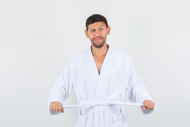 Junger mann im weißen bademantel, der seinen gürtel festzieht und lustige vorderansicht sieht.