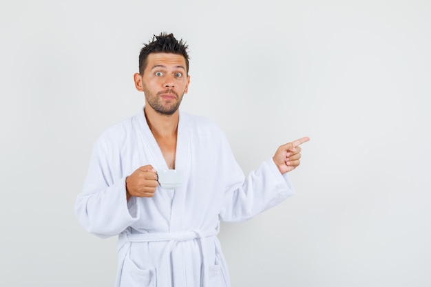 Junger mann im weißen bademantel, der weg zeigt, während tasse kaffee hält und neugierig schaut, vorderansicht.