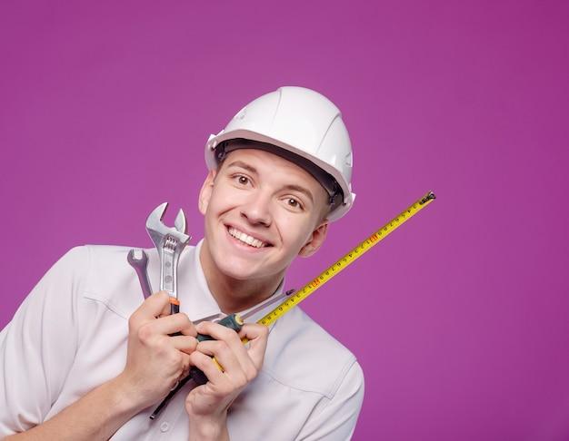 Junger mann im weißen helm mit arbeitswerkzeug in der hand auf lila hintergrund