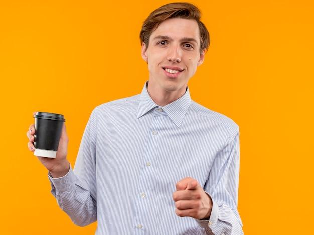 Junger mann im weißen hemd, das kaffeetasse hält, die mit dem zeigefinger zeigt, der zuversichtlich über orange wand steht