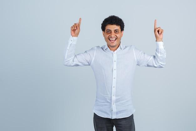 Junger mann im weißen hemd, hose zeigt nach oben und sieht glücklich aus, vorderansicht.