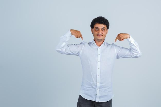 Junger mann im weißen hemd, hosen, die auf sich selbst zeigen und stolz aussehen, vorderansicht.