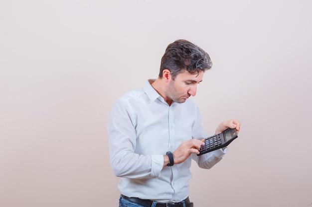 Junger mann im weißen hemd, jeans mit taschenrechner und beschäftigt aussehend looking